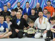 Philip Mulpeter and John Kavanagh with Conor McGregor's UFC belt