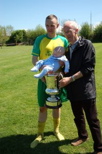 Lee Salter with his grandfather and son, holding the premier cup.