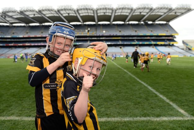 LJ Cuddy, left, helps team-mate Tadgh Lowry with his helmet, representing Camross at the Go Games in Croke Park