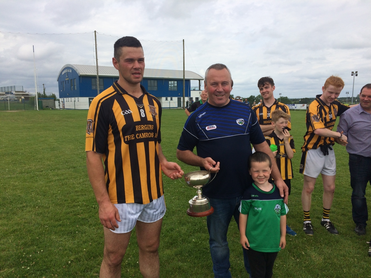 Camross captain Andrew Collier receiving the cup from Seamus Mortimer